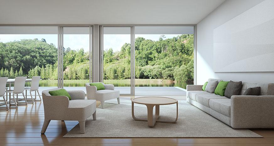 Imagen de un salón estilo lagom. A la derecha dos sillomes con las esquinas redondeadas y un cojín verde. En el centro una mesa de centro circular y en la derecha un sofá de cuatro plazas. Todo esto en color beige.