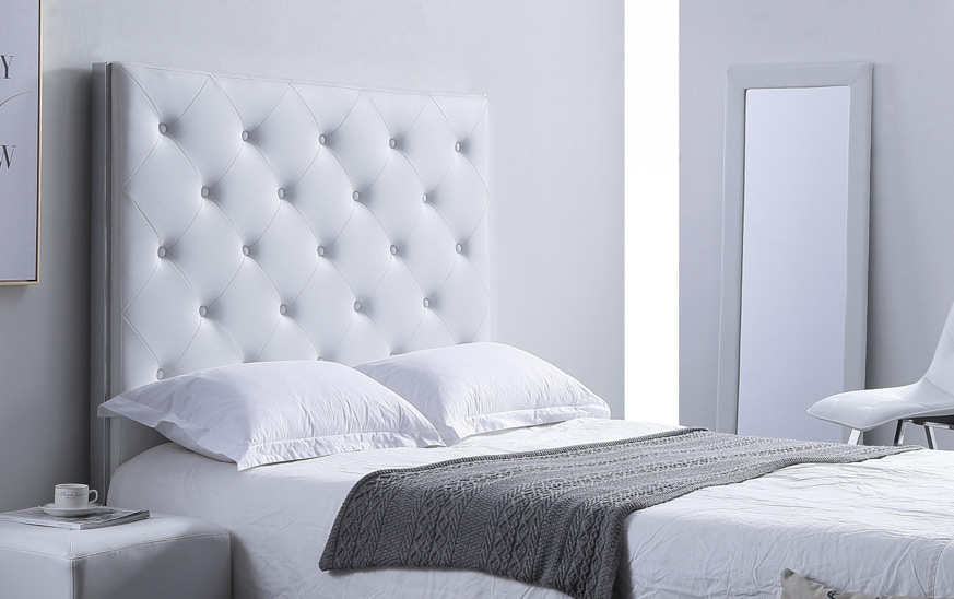 Cabecero de polipiel blanco estilo muebles neoclásicos. Imagen compuesta por un cabezal en la parte central acompañado por una cama con dos cojines. En la parte derecha hay un espejo de pie blanco. En la derecha un mesita de noche blanca con una taza encima.