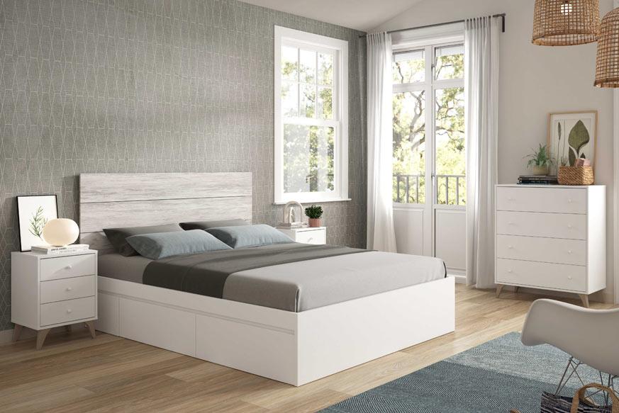 Dormitorio de matrimonio compuesto por una cama con cuatro cajones (dos en cada lateral) de color blanco, dos mesitas de noche con dos cajones, un cabecero y una cómoda de cuatro cajones. Todo esto acabado en color blanco, excepto el cabecero que es de color roble.