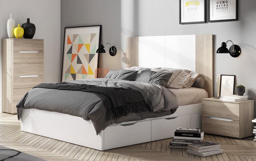 Dormitorio con una cama blanca en el centro, una mesita en la parte derecha en color roble y en la parte izquierda una cómoda de tres cajones en el mismo color.