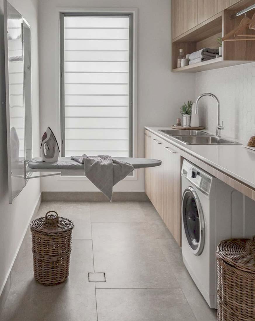 Lavanderia en casa con tabla de planchar y cesto de la ropa sucia.