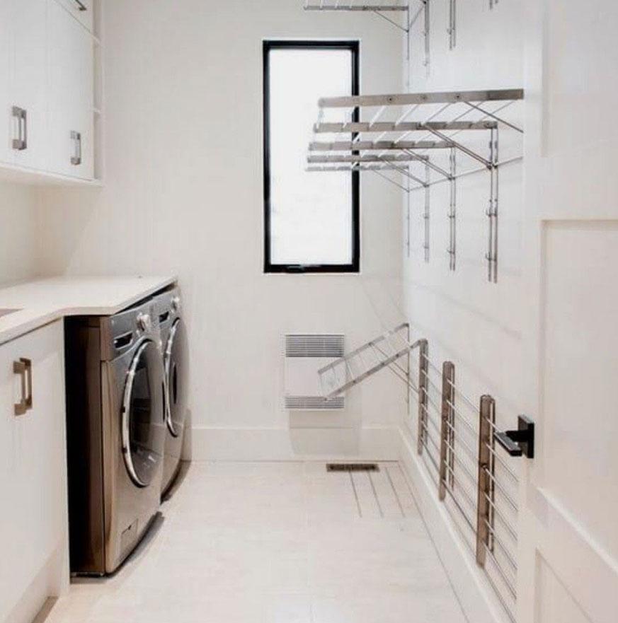 Lavandería en casa con accesorios colgadores en la pared.