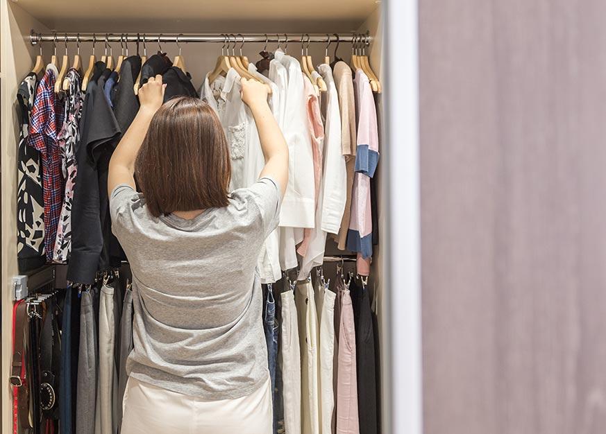 Mujer escogiendo qué ponerse en un vestidor abierto
